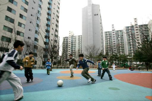 아파트 단지 놀이터에서 축구를 하는 어린이들 모습.