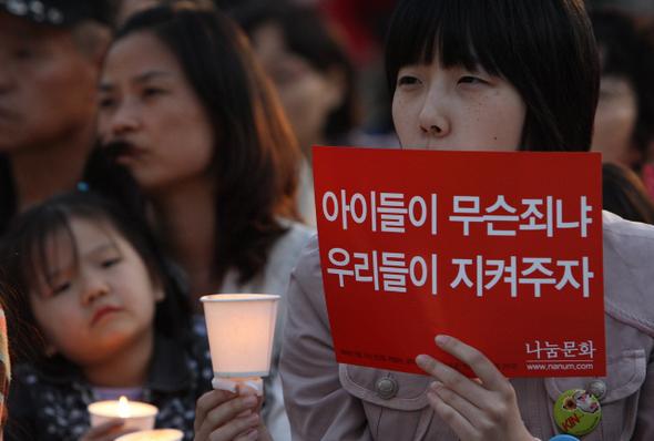 """15일 저녁 서울 시청앞 광장에서 열린 미국산 쇠고기 수입 반대 촛불문화제에 참석한 시민이 """"아이들을 지켜주자""""라고 적힌 손팻말을 들고 있다. 신소영 기자 <A href=""""mailto:viator@hani.co.kr"""">viator@hani.co.kr</A>"""
