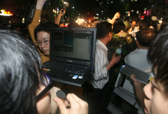 """인터넷 방송 누리집인 <아프리카> 방송 진행자들이 지난 27일 새벽 서울 종로 종각 앞에서 벌어진 촛불문화제 거리 시위에 나와 노트북을 든 채 실시간으로 중계방송을 하고 있다.  이종근 기자 <A href=""""mailto:root2@hani.co.kr"""">root2@hani.co.kr</A>"""