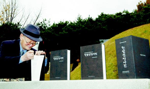 지난 2009년 11월 8일 서울 용산구 효창동 백범 김구 묘소에서 열린 '친일인명사전 발간 국민보고대회'에서 한 시민이 백범의 제단에 바쳐진 사전을 살펴보고 있다.  김명진 기자 littleprince@hani.co.kr