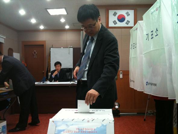경기도 성남시 분당구 분당동 제1 투표소에서 27일 아침 투표를 마친 한 유권자가 투표함에 투표용지를 넣고 있다. 사진 허재현 기자