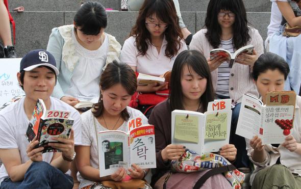 '반값 등록금 실현을 위한 북카페'가 지난 6일 저녁 서울 광화문광장 해치마당에서 열리고 있다. 행사 개최 소식을 트위터와 페이스북 등을 통해 전해듣고 참가한 시민들이 계단에 나란히 앉아 책을 읽었는데, 경찰의 집회 불허에 항의하는 새로운 형태의 '책 시위'이다.  이정우 선임기자 woo@hani.co.kr