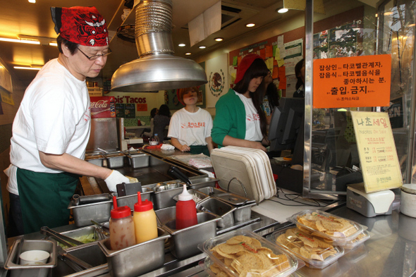 최우진 사장이 4일 오후 서울 신촌 명물거리에 있는 중소 자영업체 초이스타코 매장에서 주문받은 요리를 만들고 있다.(왼쪽) 이 가게 건너편에 들어선 미국계 다국적기업 타코벨 매장에 개업을 알리는 대형 펼침막이 걸려 있다.  이정아 기자 leej@hani.co.kr