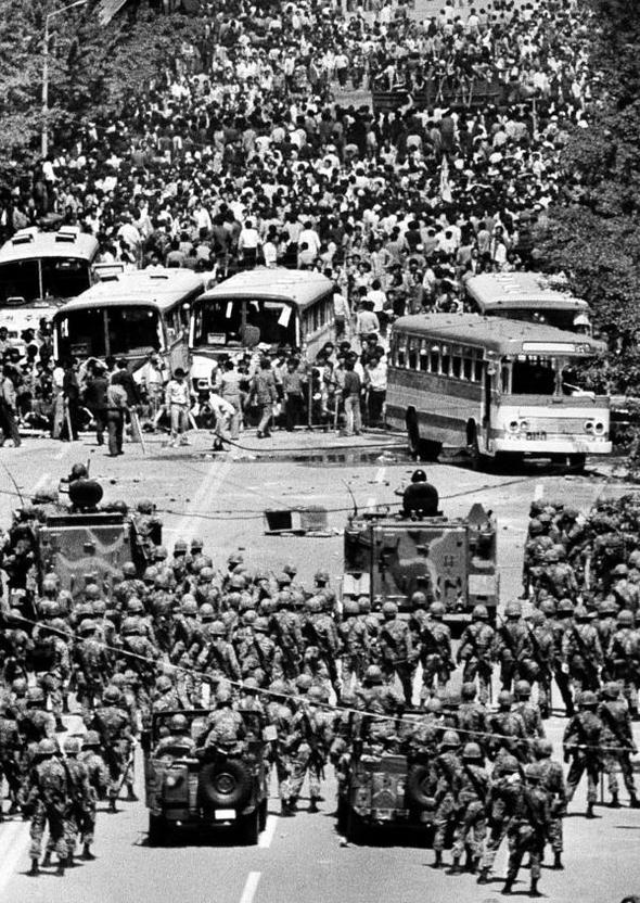 1980년 5월 21일 시민들이 전날 도청 앞 저지선을 뚫으려다 멈춘 버스를 바리케이드로 이용 계엄군과 대치하고 있다.5·18기념재단(황종건) 제공