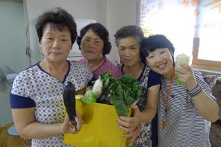 서울 노원구 월계동 사슴2단지에서 지난 12일 열린 '행복한 아파트공동체 학교' 종강식에 참가한 아파트 주민들이 카메라로 서로를 찍은 사진들 가운데 우수작을 선정하고(위쪽) 열심히 출석해 상품으로 받은 채소를 들고 있다.(아래쪽) 희망제작소 제공