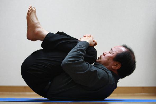 고문의 심한 후유증을 대체의학인 '역학요법'으로 극복한 정동년씨가 뒤틀린 골반과 척추를 바로잡아주는 '새우 운동'을 보여주고 있다.