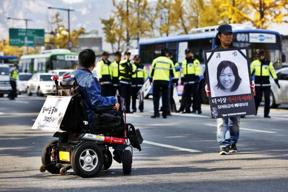 화재로 질식사한 장애여성 활동가 김주영씨의 노제를 마친 장애인들이 2012년 10월30일 '24시간 활동보조 보장'을 요구하며 서울 광화문 도로에서 시위를 하고 있다. 김명진 기자