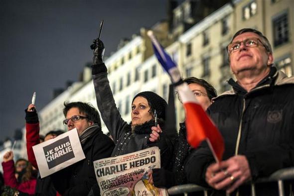 7일 프랑스 리옹에서 열린 프랑스 시사 주간지 <샤를리 에브도> 테러 사건 희생자의 추모 집회에서 한 여성이 언론을 상징하는 펜을 들고 울고 있다. AFP 연합뉴스