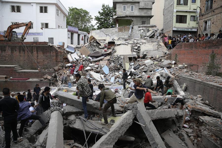 25일(현지시각) 규모 7.8 강진으로 큰 피해를 본 네팔 수도 카트만두에서 주민들이 무너진 건물 잔해를 맨손으로 들어 올리며 구조작업을 하고 있다.