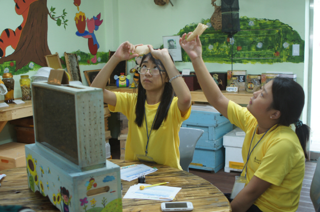 학생들이 벌집 조각의 앞뒷면을 보며 차이점을 관찰하고 있다.