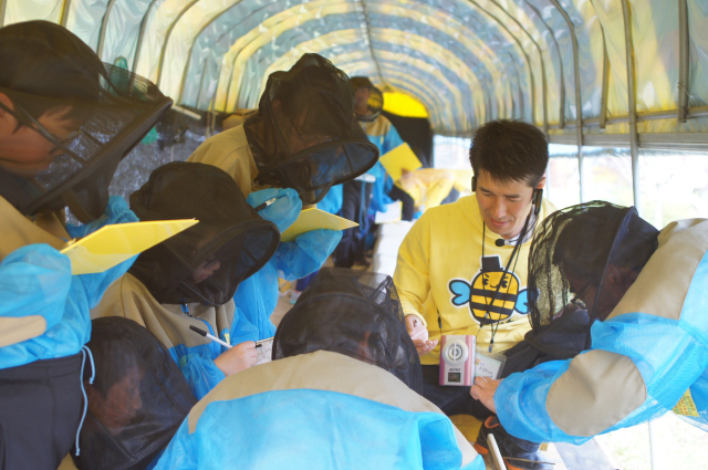 강원도 횡성군 에덴양봉원에서 학생들이 윤상복 농장주의 설명을 들으며 벌통을 보고 있다.
