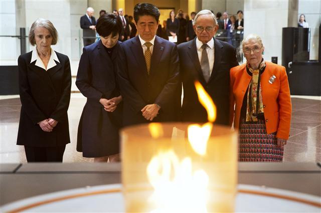 아베 신조 일본 총리(왼쪽 두번째)와 부인 아키에(왼쪽)가 27일 미국 워싱턴의 홀로코스트 기념관을 방문해, 2차대전 당시 일본 외교관 스기하라 지우네가 발급한 비자로 인해 나치의 유대인 학살을 피한 생존자들과 함께 '영원한 불꽃' 앞에서 묵념하고 있다.  워싱턴/AP 뉴시스