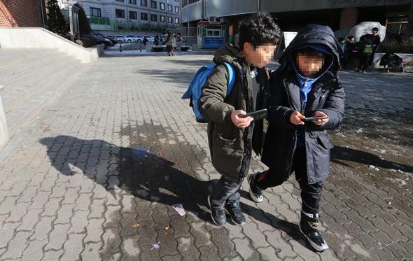 수업이 끝난 뒤 하굣길에서 스마트폰을 들여다보는 어린이들. 김정효 기자