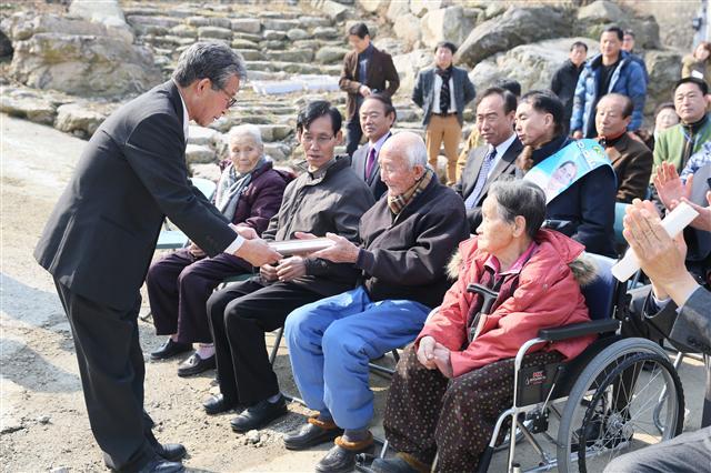 지난해 3월 유연필 쑥모시영농조합법인 대표가 마을 어르신에게 첫 연금을 지급하는 모습. 쑥모시영농조합법인 제공