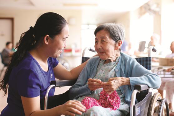 싱가포르 피스헤이븐 양로원의 한 사회복지사가 노인을 살펴보고 있다. 싱가포르 구세군 누리집 제공