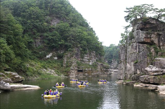 철원 한탄강 고석(사진 오른쪽 절벽) 앞 물길을 지나는 래프팅 행렬. 사진 이병학 선임기자