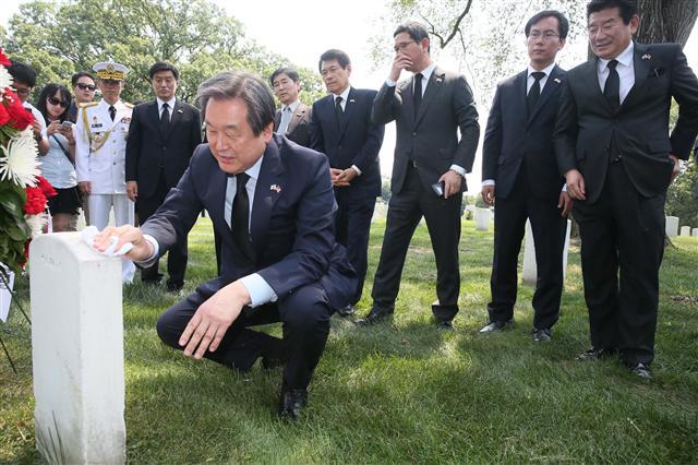 김무성 새누리당 대표가 지난 26일 워싱턴 근교 알링턴 국립묘지 내 월턴 워커 장군의 묘비에 절한 뒤 묘비를 닦고 있다. 연합뉴스