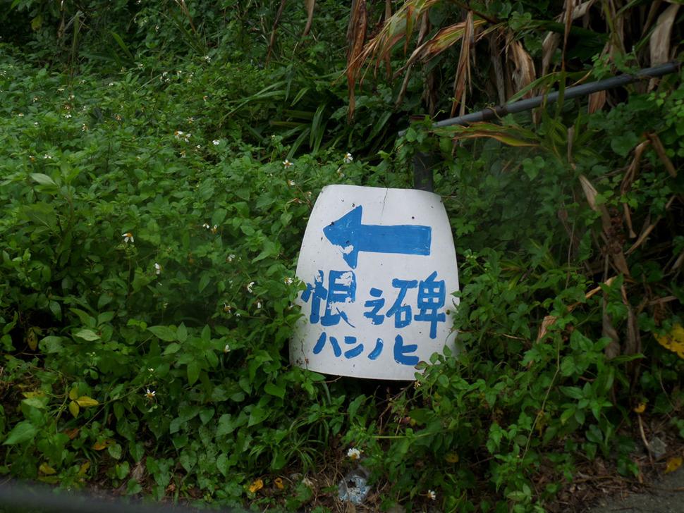 나카가미군(中頭郡) 요미탄손(讀谷村) 세나하(瀨名波)의 좁다란 시골길 옆 풀숲에 놓여 있는 '한의 비(恨の碑)' 표지판.