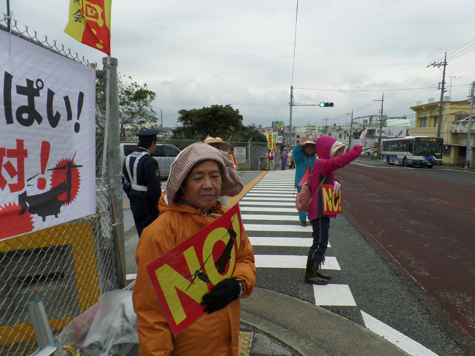 """후텐마 기지 노다케 정문에서 기지반대 시위를 벌이고 있는 68살 우에마 요시코(68)씨. 그녀는 """"전쟁(2차대전) 뒤 (미군에게) 오키나와를 빼앗겼다. 미군기지 때문에 오키나와의 자립적 사회 건설이 불가능해졌다""""고 말했다."""