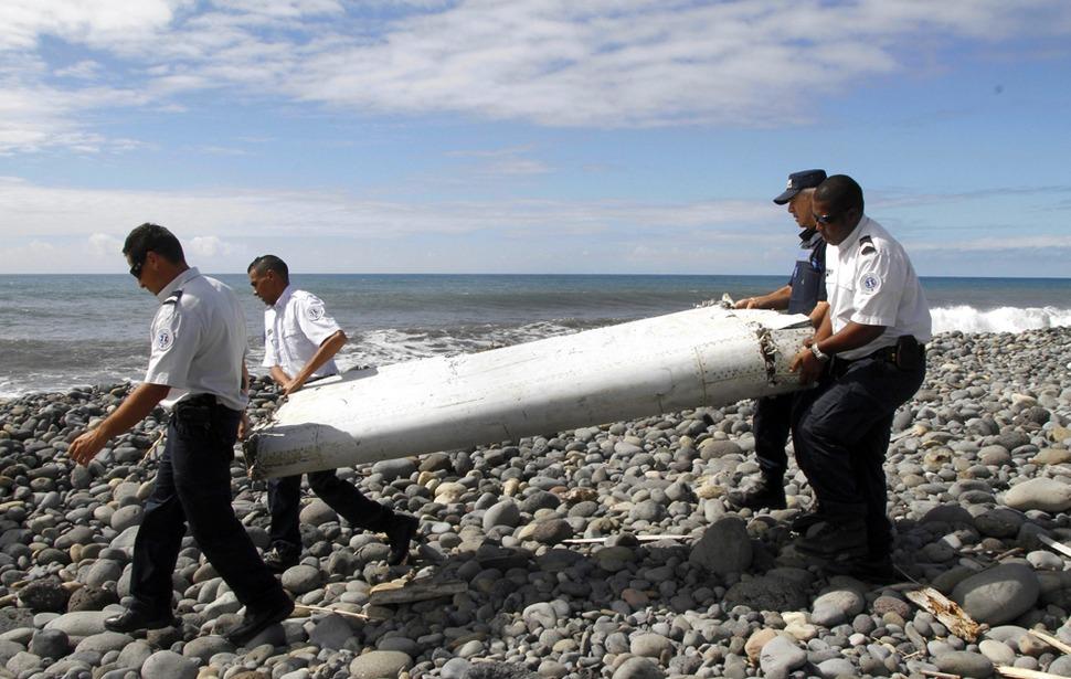 지난달 29일 프랑스령 레위니옹 섬의 동부 해안가에서 지난해 3월 실종된 말레이시아항공370의 날개의 일부로 추정되는 '플래퍼론'을 경찰이 수거하고 있다. 이 부품은 거의 손상되지 않아, 비행기가 누군가에 의해 통제된 상태로 미끄러지듯 수면 위로 착륙해 서서히 가라앉은 것 아니냐는 추정이 나오고 있다.