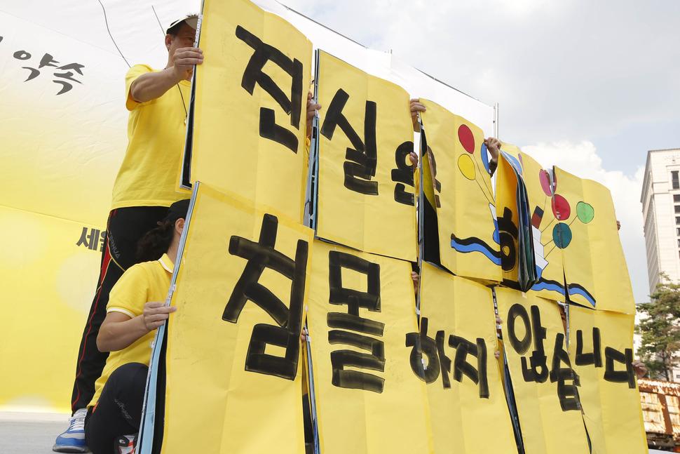 29일 오후 서울 중구 서울역광장에서 열린 세월호 참사 500일 추모 국민대회에서 참가자들이 '진실은 침몰하지 않는다'라고 적힌 플랜카드 들고 있다. 이정아 기자