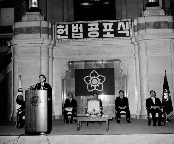 1972년 10월17일 박정희가 비상계엄령과 함께 발표한 유신헌법은 11월21일 국민투표에서 91.5%의 압도적 찬성률로 통과됐다. 이어 12월27일 박정희는 장충체육관에서 8대 대통령에 취임함으로써 장기집권의 길로 들어선다. 사진은 같은 날 서울 중앙청 중앙홀에서 총리 김종필이 유신헌법 공포식을 진행하고 있는 모습.  <한겨레> 자료사진