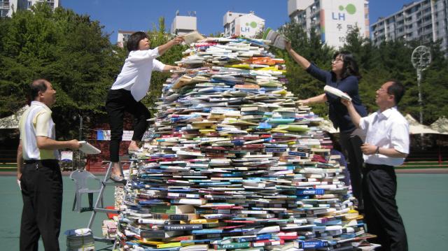 '2015년 군포 독서대전'(11~13일)을 앞둔 9일 오후 경기도 군포시 중앙공원에서 시 직원들이 책 4500권으로 '책 나무'를 만들고 있다. 사진 홍용덕 기자