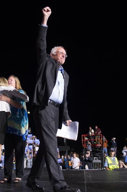 미국 민주당 대선 경선에 출마한 버니 샌더스 상원의원이 지난 14일 버지니아주 프린스윌리엄 카운티의 머내서스 유세에서 연설을 하기 위해 무대로 오르며 손을 치켜들고 있다.  머내서스/AP 뉴시스