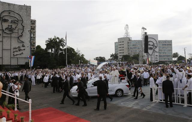 프란치스코 교황이 20일 쿠바 수도 아바나의 혁명광장에서 미사를 집전하기 위해 차를 타고 들어서고 있다. 뒤에 보이는 정부기관 건물에는 쿠바 혁명가인 카밀로 시엔푸에고스의 얼굴을 묘사한 금속 조형물이 붙어 있다.  아바나/AP 연합뉴스