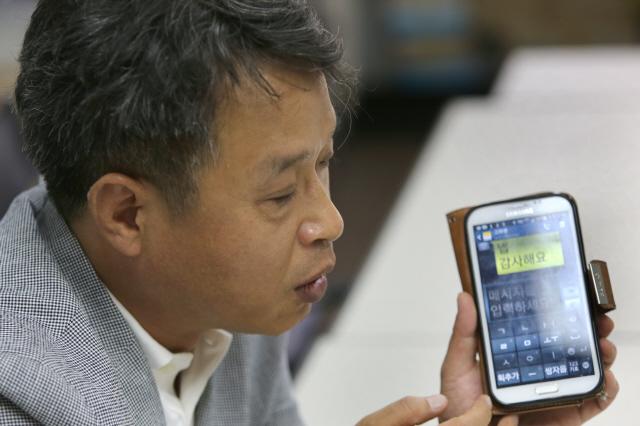 1급 시각장애인인 이건범 대표가 스마트폰의 큰 자판을 이용해 문자메시지를 보내는 방법을 설명하고 있다.  탁기형 선임기자
