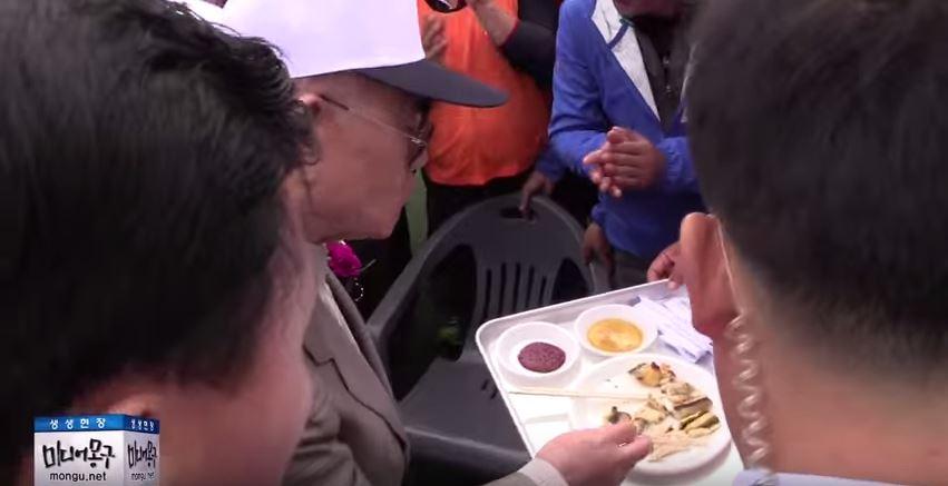 전두환 전 대통령이 한 참석자가 준비한 음식을 맛보고 있다. 미디어 몽구 취재 영상 화면 갈무리.