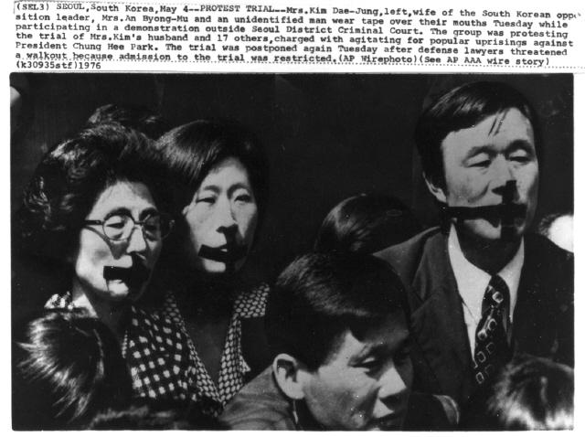 1976년 5월4일 '3·1 명동성당 사건' 첫 공판이 비공개되자 구속자 가족들은 이희호의 제안대로 검정 테이프를 입에 붙이고 침묵시위를 벌여 항의했다. 사진은 그날 정동 서울형사지법 대법정 뒤편에서 십자가형 검정 테이프를 붙인 이희호와 김옥두 비서 등이 김대중의 출정을 기다리고 있는 모습으로, <에이피> 통신이 전세계에 전송했다.  사진 김대중평화센터 제공
