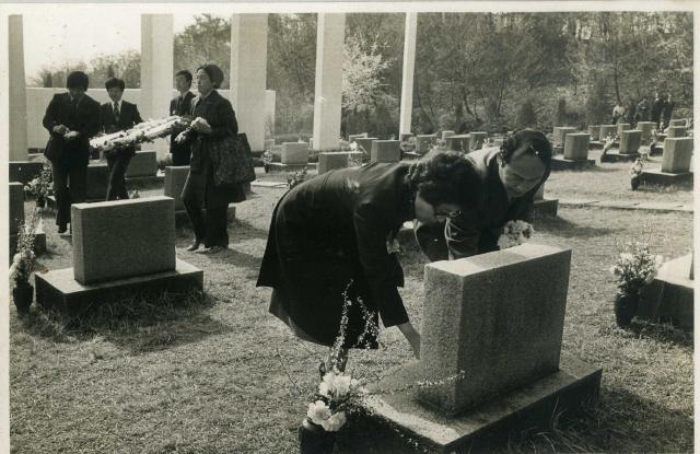 1976년 '3·1 사건' 이후 4·19 혁명일을 맞아 구속자 가족들과 수유리 묘지를 찾은 이희호(왼쪽)는 사이비 단체들이 '김대중 화환'을 치워버리자 꽃송이를 뽑아 186기의 묘비마다 한송이씩 헌화를 했다. 사진은 외신기자들로부터 비서 김형국(오른쪽)이 받아 보관해온 것으로 이번에 처음 공개했다.
