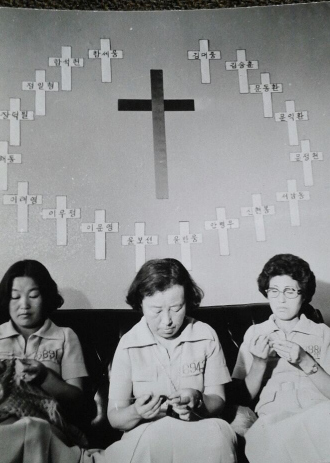 1976년 '3·1 명동성당 사건' 구속자 가족들은 서울 종로5가 기독교회관 안에 있던 천주교인권위원회 사무실에 모여 줄기차게 양심범 석방운동을 벌였다. 사진은 구속자 이름마다 형량을 적은 십자가를 붙여놓은 사무실에서 이희호·박용길·이종옥(오른쪽부터)이 나란히 앉아 애국심을 상징하는 보라색 원피스를 맞춰 입고, 브이자형 '빅토리 숄'을 뜨개질하고 있는 모습.  사진 김대중평화센터, 이종옥씨 제공