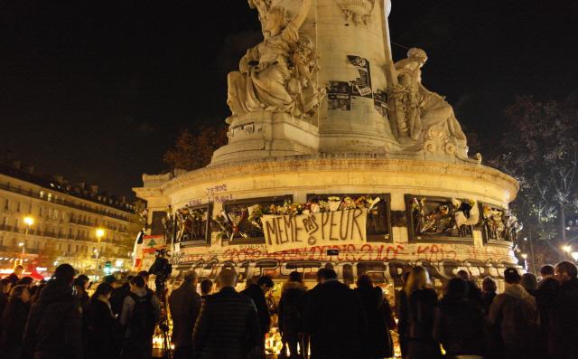 """15일 프랑스 파리 공화국 광장에서 시민들이 마리안 동상 아래 꽃과 촛불을 놓고 테러 희생자들을 추모하고 있다. 동상에는 프랑스어로 '두려워하지 않는다'(MEME PAS PEUR)라고 쓰인 펼침막이 걸렸다.  파리/조일준 기자 <a href=""""mailto:iljun@hani.co.kr"""">iljun@hani.co.kr</a>"""