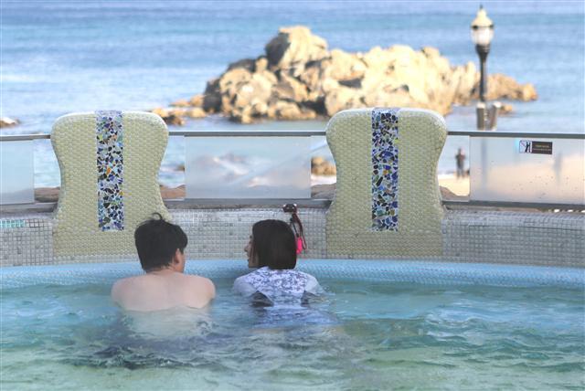 양양 대명 쏠비치 리조트 '아쿠아월드'의 해변 노천탕. 남녀 한쌍이 뜨거운 물에 몸을 담근 채 이야기를 나누고 있다.
