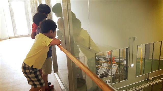 1. 충북 괴산자연드림파크에 위치한 ㈜해피푸르츠 공방 안 견학 통로를 따라 조합원 자녀들이 투명창 너머 생산 시설을 둘러보고 있다.