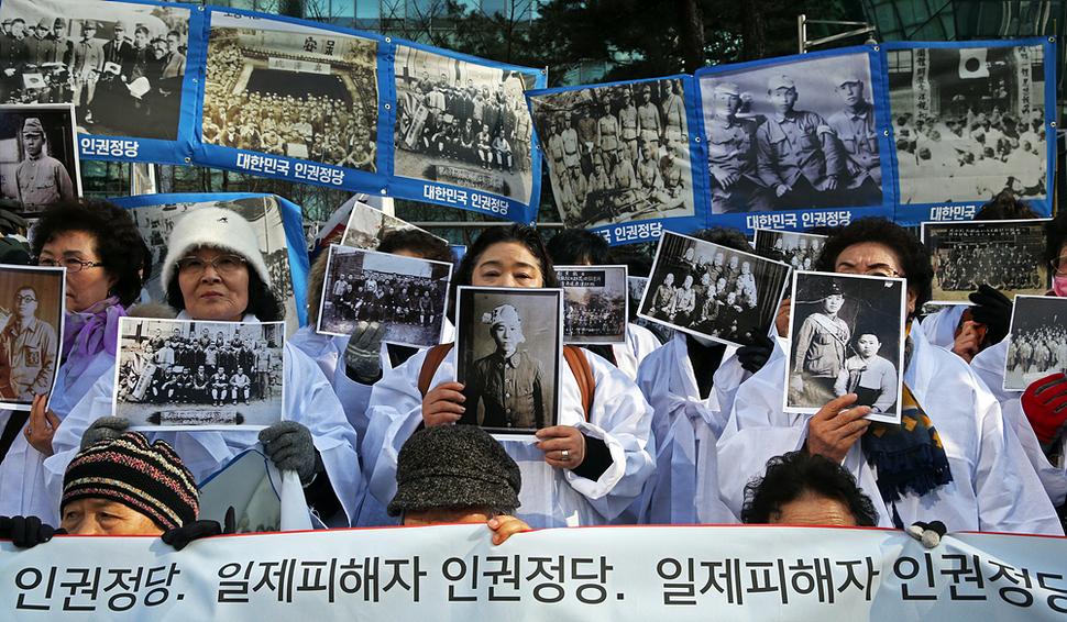 일제 강제동원 피해자 가족들이 3일 오후 서울 중학동 주한일본대사관 앞에서 흰 소복을 입은 채 정부의 일본군 위안부 협상을 규탄하고 '인권정당' 창단 선언을 하며 피해 가족의 사진을 들고 있다. 이정용 선임기자 lee312@hani.co.kr