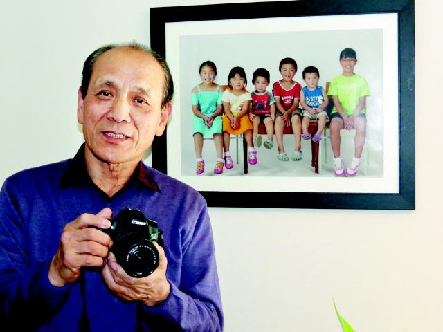 한용외 인클로버재단 이사장이 지난달 5일 서울 송파구 올림픽로에 있는 재단 사무실에서 카메라를 들고 자세를 잡았다. 한 이사장 오른쪽 뒤 벽에 걸려 있는 사진은 그가 찍은 다문화가정 가족사진이다. 곽윤섭 선임기자