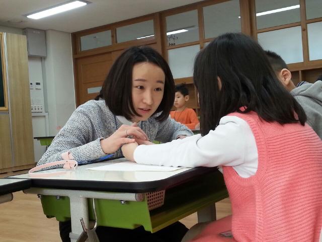 크레파스를 짝꿍과 나눠 쓰려 하지 않는 아이를 설득하고 있는 이지영 교사. 허재현 기자