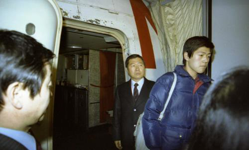 1982년 12월23일 김대중과 이희호는 아들 홍업·홍걸과 함께 미국 망명길에 올랐다. 서울대병원 뒷마당에서 구급차에 실려 김포공항에 도착한 가족은 애초 예약한 대한항공이 아닌 미국적 노스웨스트항공에 몰래 태워졌다. 취재진과 환송객을 따돌리기 위한 '비밀 추방 작전'이었다. 12월23일 저녁 김포공항에 대기 중인 노스웨스트 항공기 트랩 앞에 도착한 앰뷸런스에서 내린 김대중(왼쪽)과 막내아들 홍걸(오른쪽)의 모습.  사진 김대중평화센터 제공