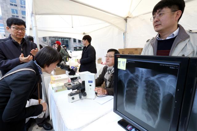 24일 오전 서울 청계천 광통교에서 열린 제6회 결핵 예방의 날 '빨간 신발끈 캠페인' 행사에서 한 시민이 결핵균을 현미경으로 살펴보고 있다. 오른쪽은 결핵환자의 엑스레이 폐사진. 김태형 기자 xogud555@hani.co.kr