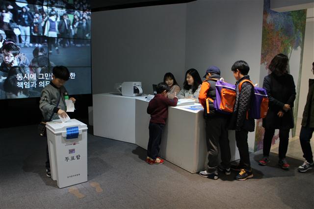 4. 전시를 찾은 학생들이 1층 선거체험관에서 사전투표체험을 하고 있다.  최화진 기자