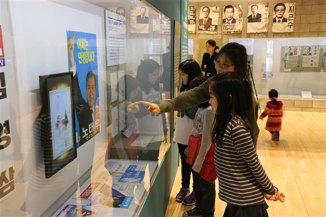 1. 지난달 26일 서울 광화문 대한민국역사박물관에서 열린 '선거, 민주주의를 키우다' 전시에서 관람객들이 전시 자료를 보고 있다.   중앙선관위 제공