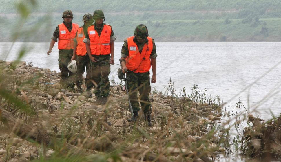 오타와협약에 불참한 미국 정부 핑계가 '지뢰 없이는 북한으로부터 남한을 보호하기 힘들다'는 이른바 한반도 예외정책이었다. 한반도 생존이 달린 사안을 놓고 정작 국내 언론은 추적 보도에 소홀했다. 홍수에 떠내려온 지뢰를 찾고 있는 군인들. <한겨레> 자료사진