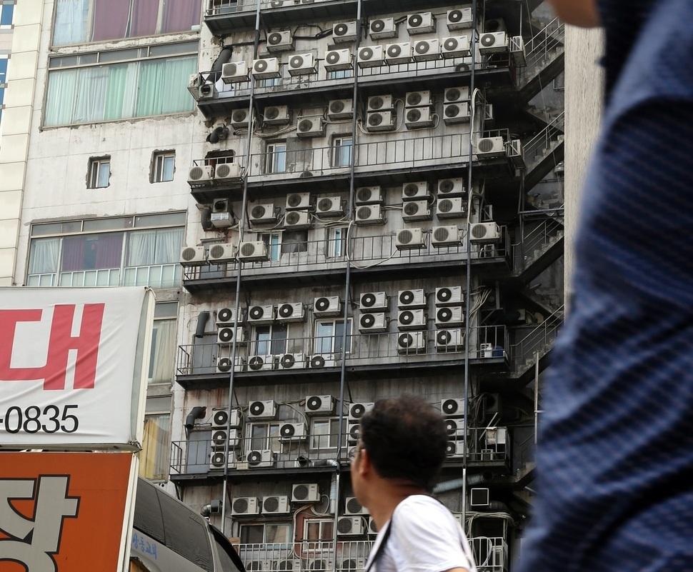 가정용 전기요금 누진제도의 개선을 요구하는 시민들의 목소리가 높아지고 있다. 서울 남대문시장을 지나던 시민이 건물 외벽에 촘촘히 설치된 에어컨 실외기들을 바라보고 있다. 김경호 선임기자 jijae@hani.co.kr
