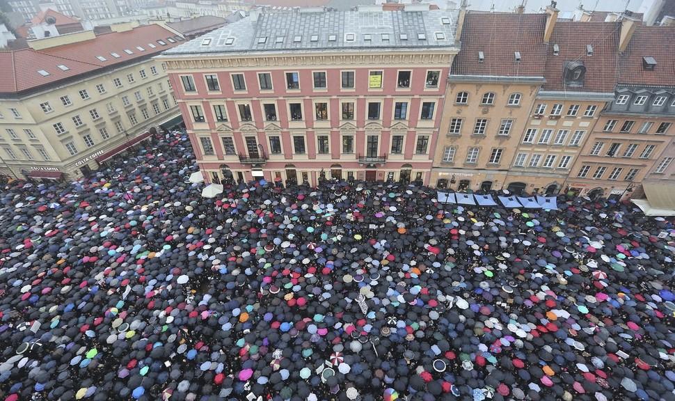 지난 3일 폴란드 수도 바르샤바 중심가의 광장에서 집권 극우 정당의 낙태 전면 금지법에 반대하는 시위대가 우산을 쓰고 시위를 벌이고 있다. 바르샤바/AP 연합뉴스
