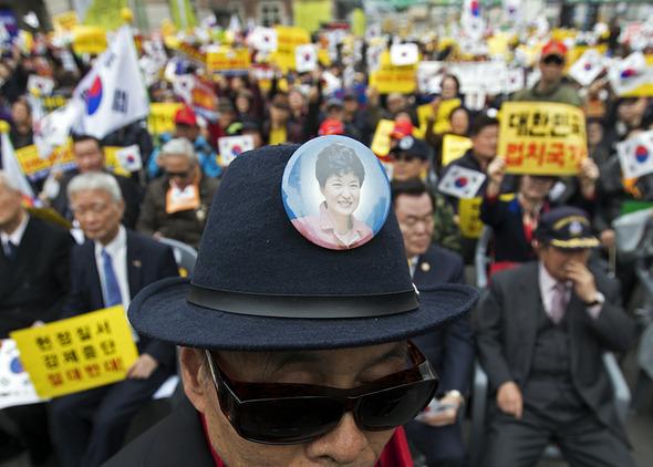 19일 오후 서울역 광장에서 열린 헌법 수호위한 국민의 외침 집회에서 박 대통령 팬클럽 박사모(박근혜를 사랑하는 모임) 회원이 모자에 박 대통령 얼굴이 있는 배지를 달고 있다. 사진공동취재단