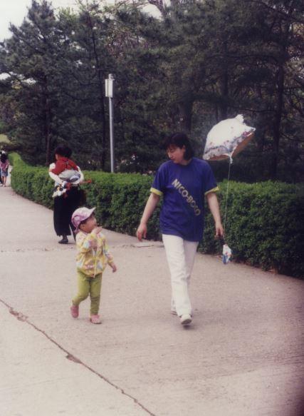 """4살 때인 1993년 엄마와 함께 공원을 걷고 있는 이길보라씨. 수화로 """"옥수수""""라 말하고 있다. 이길보라씨는 유치원에 가서야 말을 배웠다. 이길보라 제공"""