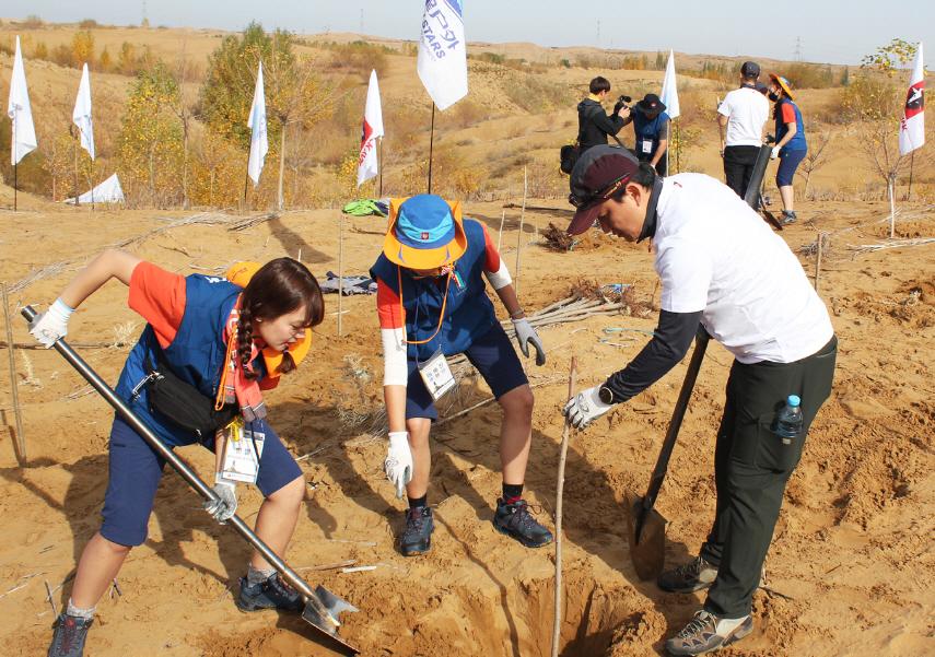 아웃도어 업체 블랙야크가 운영하는 블랙야크강태선나눔재단이 지난 10월 자원봉사자들과 함께 중국 네이멍구 쿠부치 사막에서 '희망 나무 심기' 활동을 펼치고 있다. 블랙야크 제공